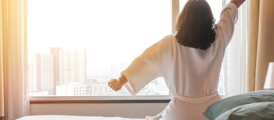 Woman waking up in hotel room