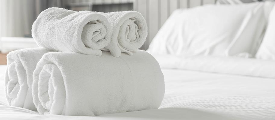 Hotel towels folded on bed